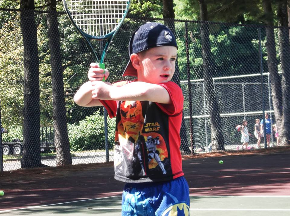 This is a photo of a child holding a tennis racket at JCamp