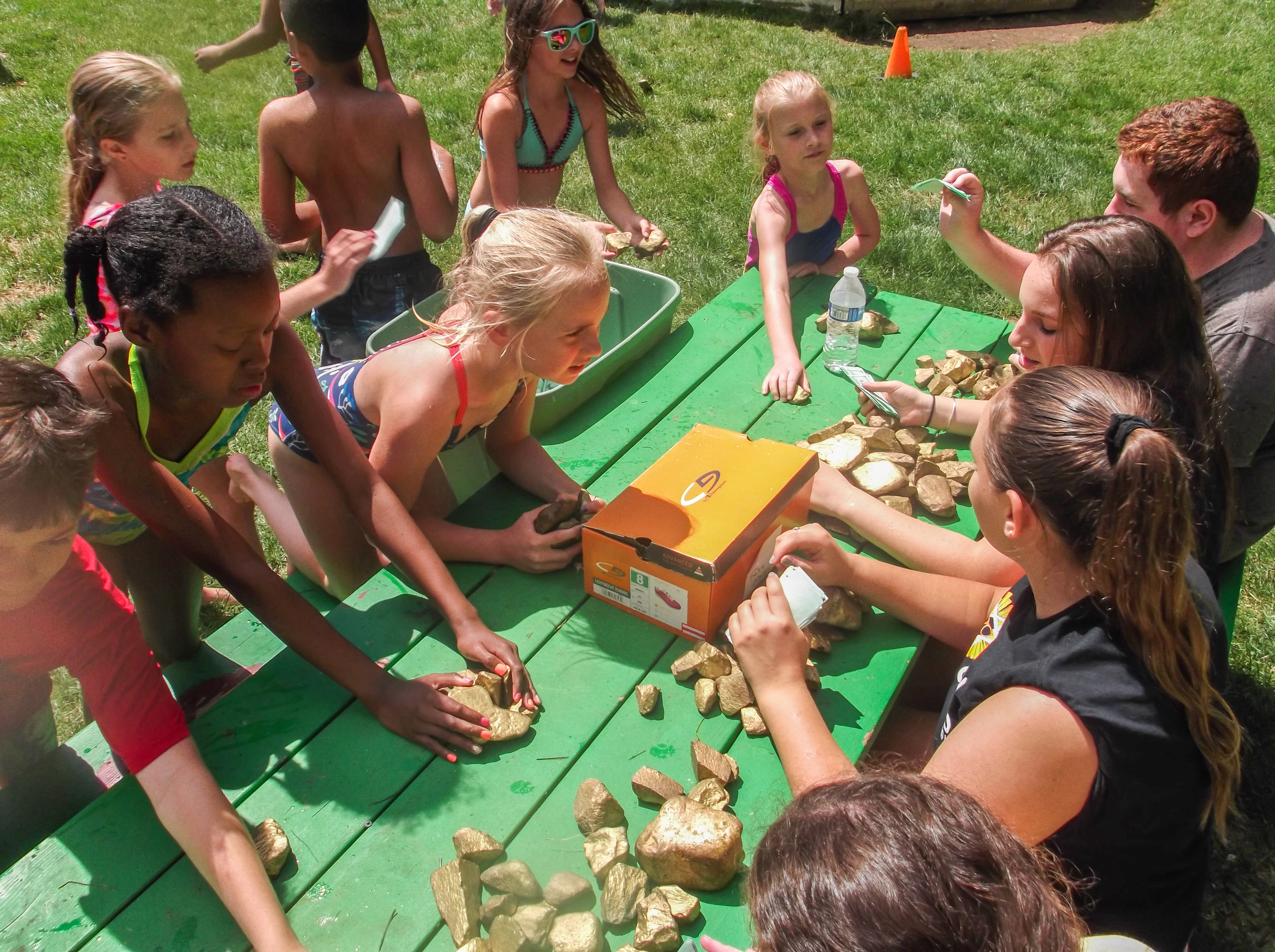 This is a photo of children at the JCC Summer Camp with gold rocks on a picnic table